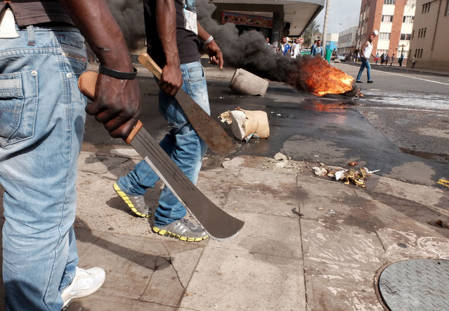 In this photo taken Tuesday, April 14, 2015, immigrant men armed with machetes make their way onto a Durban, South Africa, street during clashes with police and in search of locals that attacked foreign shop owners in the city center. (Photo by Tebogo Letsie/AP Photo)
