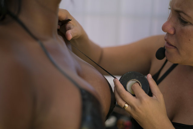 In this January 11, 2017 photo, Erika Martins uses black electrical tape to create a customer's bikini, in order to attain crisp tan lines, on her rooftop Erika Bronze salon in the suburb of Realengo in Rio de Janeiro, Brazil. Martins wears a microphone connected to an open speaker system in order to direct her assistants to clients who need more tanning lotion or a sprinkling of water on their skin. (Photo by Renata Brito/AP Photo)