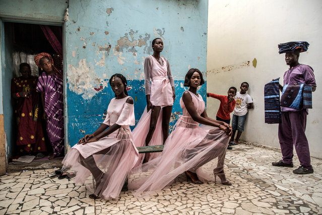Portraits single nominee: Dakar fashion, by Finbarr O'Reilly. Curious residents and a street vendor selling material look on as models Diarra Ndiaye, Ndeye Fatou Mbaye and Malezi Sakho wear outfits by the Senegalese designer Adama Paris in the Medina neighbourhood of Senegal's capital, Dakar. (Photo by Finbarr O'Reilly/World Press Photo 2019)
