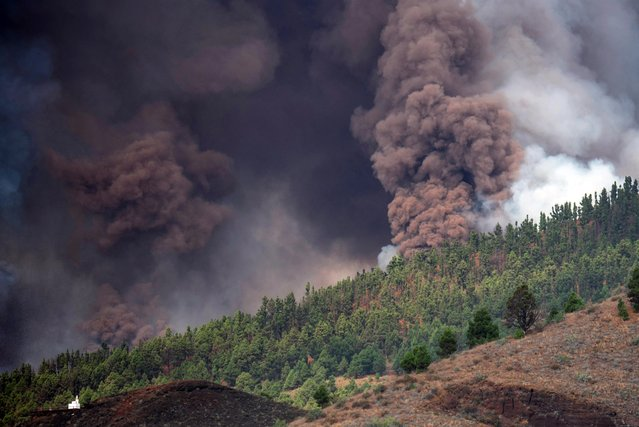Mount Cumbre Vieja erupts spewing out a column of smoke, ash and lava as seen from Los Llanos de Aridane on the Canary island of La Palma on September 19, 2021. (Photo by Desiree Martin/AFP Photo)