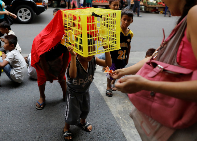 A passer-by gives money to children performing lion dance using makeshift costumes on the Lunar New Year eve in Manila's Chinatown, the Philippines January 27, 2017. (Photo by Erik De Castro/Reuters)