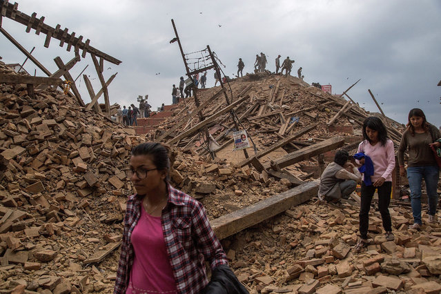 People stand on top of debris from a collapsed building at Basantapur Durbar Square watching the destruction following an earthquake on April 25, 2015 in Kathmandu, Nepal. (Photo by Omar Havana/Getty Images)