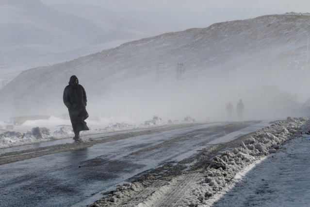 A man walks near snow on the closed off Damascus to Homs highway, Syria January 28, 2017. (Photo by Omar Sanadiki/Reuters)