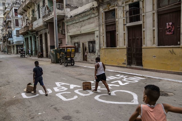 """Children play on a street that has graffiti reading is Spanish """"Put your heart on Cuba"""", in Havana, Cuba, Monday, July 26, 2021. (Photo by Eliana Aponte/AP Photo)"""