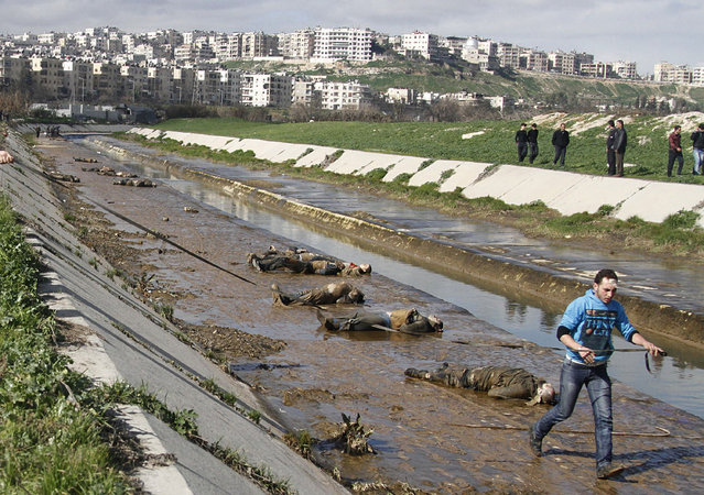 In this January 29, 2013, file photo, a man walks past dead bodies in front of a river in the neighborhood of Bustan al-Qasr in Aleppo, Syria. (Photo by Abdullah al-Yassin/AP Photo)
