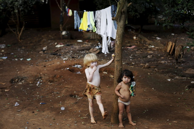 Guarani Indian boys stand in the village of Pyau at Jaragua district, in Sao Paulo April 27, 2015. (Photo by Nacho Doce/Reuters)