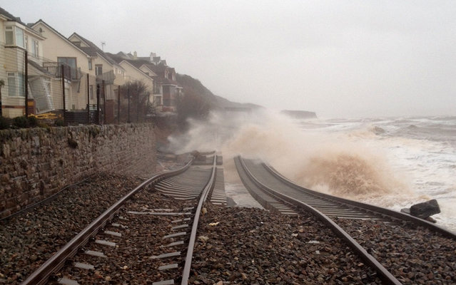 A handout picture released by Network Rail on February 5, 2014 shows waves whipped up by stormy weather crashing over train lines in Dawlish in south Devon, southern England, on February 5, 2014. More than 8,000 homes were without power in southwest England after fresh storms battered the region, sending huge waves crashing onto the coastline and damaging sea defence. (Photo by AFP Photo/Network Rail)