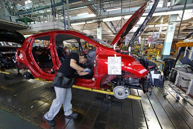 Employees works on the automobile assembly line of a Renault Clio IV at the Renault automobile factory in Flins, west of Paris, France, May 5, 2015. (Photo by Benoit Tessier/Reuters)