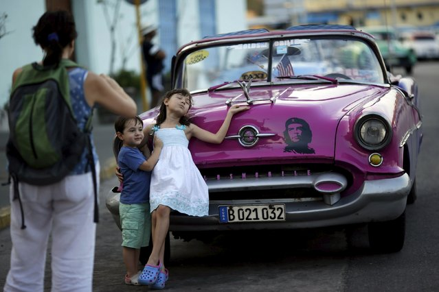 Young U.S. visitors pose for a photograph next to a vintage car in Havana March 16, 2016. (Photo by Ueslei Marcelino/Reuters)