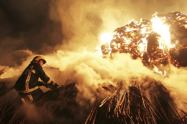 A firefighter attempts to extinguish a fire which broke out on piles of reed at a paper factory in Changde, Hunan province, on February 16, 2014. (Photo by Reuters/Stringer)