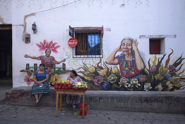 Maya Tz'utujil women sell fruit in San Juan La Laguna, Guatemala, Tuesday, March 12, 2019. An English tourist whose body was found near a Guatemala highland lake popular with travelers died of hemorrhaging resulting from a traumatic brain injury, according to an autopsy report completed Tuesday. (Photo by Santiago Billy/AP Photo)