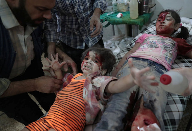 A Syrian girl cries out as a wounded child lies next to her at a makeshift hospital on 12 September 2016. She had been injured in reported government airstrikes on the rebel-held town of Douma, east of Damascus, Syria. (Photo by Abd Doumany/AFP Photo/Courtesy of World Press Photo Foundation)