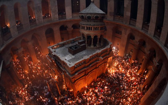 """Christian Orthodox worshippers hold up candles lit from the """"Holy Fire"""" as they gather in the Church of the Holy Sepulchre in Jerusalem's Old City on April 27, 2019 during the Orthodox Easter. The ceremony celebrated in the same way for eleven centuries, is marked by the appearance of """"sacred fire"""" in the two cavities on either side of the Holy Sepulchre. (Photo by Thomas Coex/AFP Photo)"""