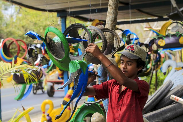 Juan Salazar (15), paints a bird figurine made of recycled tyres to be sold in a shop located on the Panamerican highway near Catarina town May 7, 2015. (Photo by Oswaldo Rivas/Reuters)