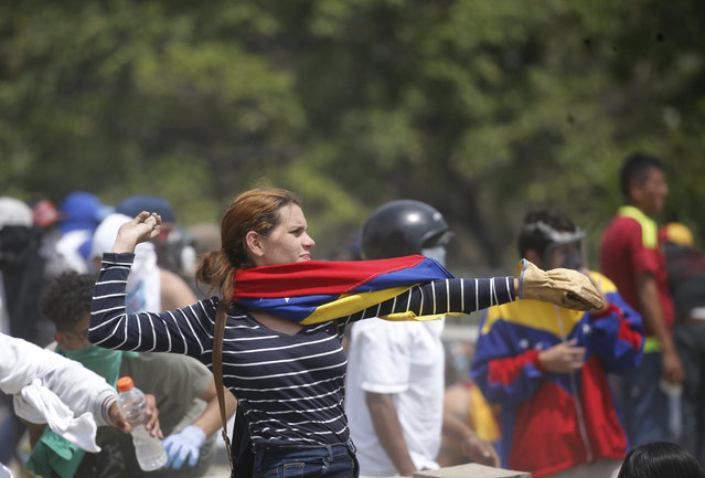 An anti-government protester throws a rock toward La Carlota airbase from where security forces fire tear gas at demonstrators in Caracas, Venezuela, Wednesday, May 1, 2019. (Photo by Ariana Cubillos/AP Photo)