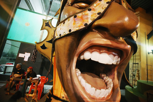Workers sit by a part of a float at a samba school warehouse on February 24, 2014 in Rio de Janeiro, Brazil. Carnival officially begins on February 28 but pre-festivities have already begun. Brazil is gearing up to host the 2014 FIFA World Cup. (Photo by Mario Tama/Getty Images)