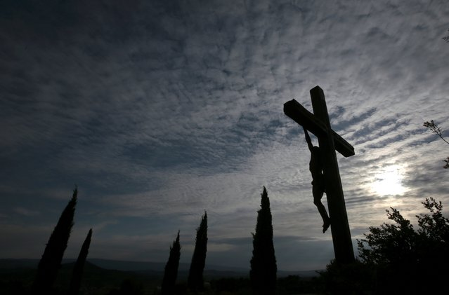 A crucifix is seen at sunset in the village of Saint Saturnin les Apt in the Luberon, southern France, April 29, 2015. (Photo by Eric Gaillard/Reuters)