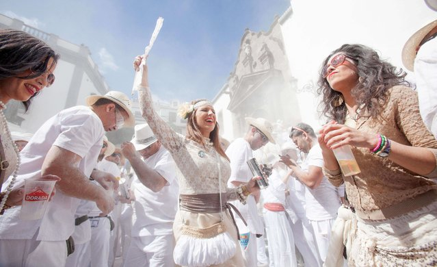 "People throw talcum powder as they take part in the carnival of ""Los Indianos"" (the Indians) in Santa Cruz de la Palma, on the Spanish Canary island of Las Palma on March 3, 2014. (Photo by Desiree Martin/AFP Photo)"
