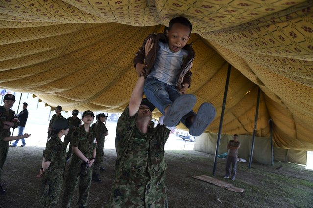 Eight year old Nepalese child Nisan reacts as he plays with Japanese doctor Mazaki Miyazaki in a tent camp in Kathmandu on May 5, 2015, which was set up for people that were left homeless after their houses were destroyed on the April 25 deadly earthquake that killed over 7,300 people and left tens of thousands homeless. (Photo by Roberto Schmidt/AFP Photo)