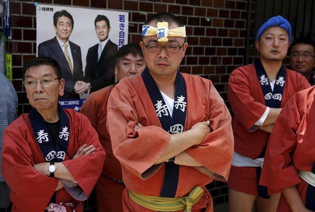 Revellers stand in front of an election poster showing Japanese Prime Minister Shinzo Abe (back L) as they watch a portable shrine paraded through a street during the Sanja Matsuri festival in the Asakusa district of Tokyo May 17, 2015. (Photo by Thomas Peter/Reuters)