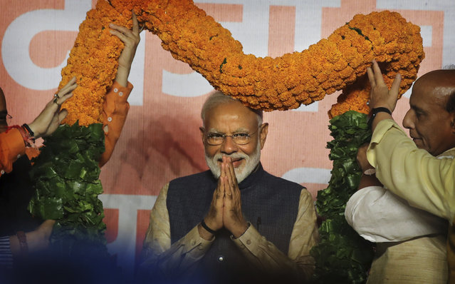 Indian Prime Minister Narendra Modi receives a giant floral garland from party leaders at their headquarters in New Delhi, India, Thursday, May 23, 2019. Indian Prime Minister Narendra Modi's party claimed it had won reelection with a commanding lead in Thursday's vote count, while the stock market soared in anticipation of another five-year term for the pro-business Hindu nationalist leader. (Photo by Manish Swarup/AP Photo)