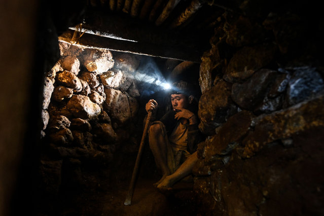 This photo taken on May 16, 2019 shows a miner working in a tunnel in a ruby mine in Mogok, north of Mandalay. (Photo by Ye Aung Thu/AFP Photo)