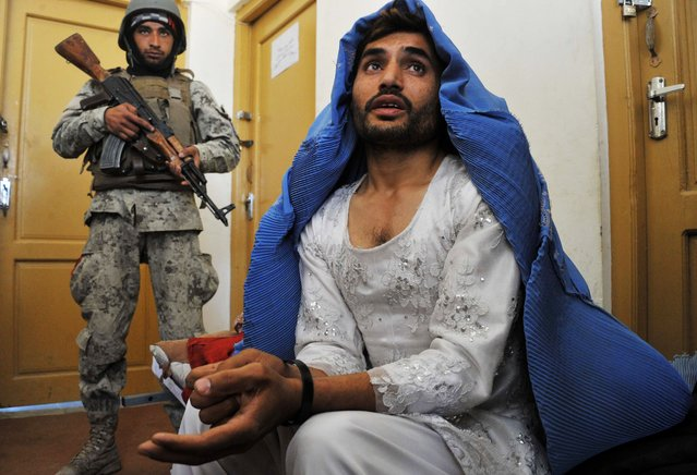 Afghan security personnel present a burqa-clad resident they say is a Taliban fighter to the media at the Afghan National Army headquarters in Khogyani District near Jalalabad on March 18,2014. Three Taliban insurgents have been arrested in possession of heroin by Afghan Joint Forces during an operation in the Khogyani District of Nangarhar province. (Photo by Noorullah Shirzada/AFP Photo)