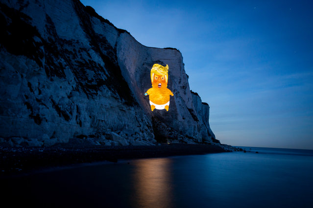A giant projection of the Trump Baby lit up the White Cliffs of Dover on 1st June 2019 in Dover, United Kingdom. With the US President arriving in the UK this week, campaigners from the Trump Baby team, illuminated the cliffs with a projection of the baby. Trumps visit is expected to be met by widespread protest. The Trump Baby Inflatable, which captured the publics mood last time the President visited, is set to fly on Tuesday but only if a fundraising target of £30,000 is met to support groups affected by Trumps presidency. (photo by Andrew Aitchison/In Pictures via Getty Images)