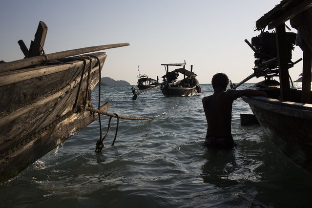 Nguy, an indigenous Moken man, takes his boat out as the tide comes in. The boat on the left (identified by it's unique prow design) is one of only a few Kabang left in the world. Traditionally, Moken would live most of the year aboard Kabang and each boat would hold a nuclear family. February 27, 2013 – Ko Surin, Thailand. (Photo by Taylor Weidman/zReportage via ZUMA Press)