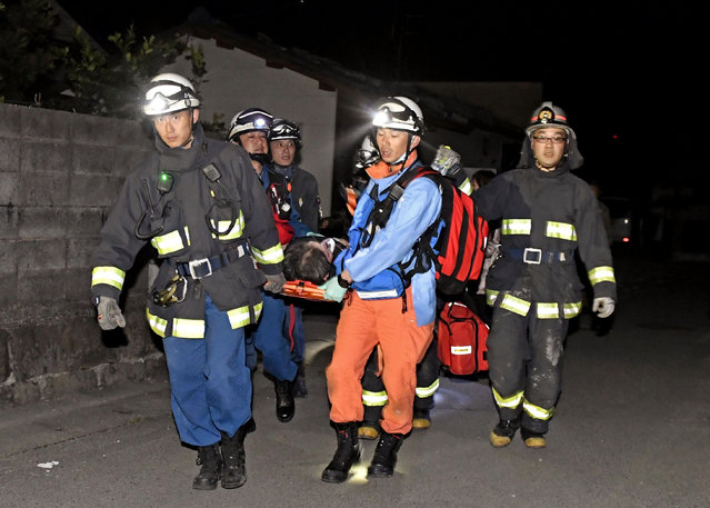 Firefighters carry an injured after the earthquake, at the town of Mashiki, in Kumamoto, southern Japan, Thursday, April 14, 2016. A powerful earthquake with a magnitude of 6.5 knocked over buildings in southern Japan on Thursday evening, and police said people may be trapped underneath. (Photo by Kyodo News via AP Photo)