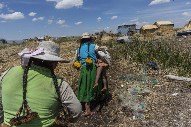 In this February 2, 2017 photo, a woman carries her baby home in Kapi Cruz Grande, a village on the trash filled shores of Lake Titicaca in the Puno region of Peru. Peru's new president, Pedro Pablo Kuczynski, a former Wall Street banker who lived just 40 kilometers (25 miles) from the lake as a youth, has made access to clean water one of the priorities of his presidency. (Photo by Rodrigo Abd/AP Photo)