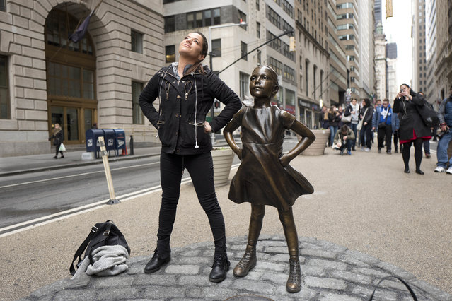 "A woman strikes a pose in front of a statue titled ""Fearless Girl"" on Wednesday, March 8, 2017, in New York. A big investment firm, State Street Global Advisors, put the statue there to highlight International Women's Day. The work by artist Kristen Visbal. (Photo by Mark Lennihan/AP Photo)"