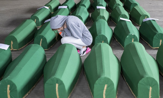 A girl inspects coffins prepared for burial, in Potocari near Srebrenica, Bosnia, Wednesday, July 10, 2019. The remains of 33 victims of Srebrenica massacre will be buried on July 11, 2019, 24 years after Serb troops overran the eastern Bosnian Muslim enclave of Srebrenica and executed some 8,000 Muslim men and boys, which international courts have labeled as an act of genocide. (Photo by Darko Bandic/AP Photo)