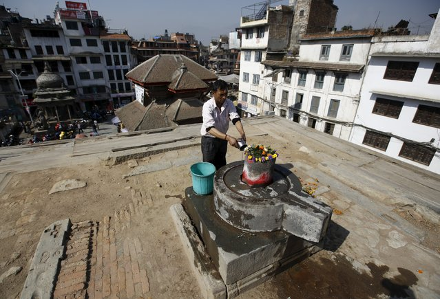 A man offers prayers at the site of a collapsed temple during the first anniversary of the earthquake in Kathmandu, Nepal, April 24, 2016. (Photo by Navesh Chitrakar/Reuters)