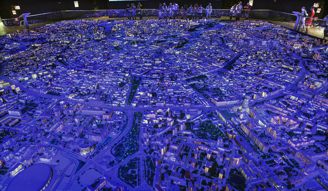 """Visitors inspect the exhibition """"The Model of Moscow"""" in Moscow on July 19, 2019. The architectural model of Moscow represents 19,843 buildings inside the Garden Ring and partly outside it, in the area of 369 square meters on a scale of 1:400. (Photo by Alexander Nemenov/AFP Photo)"""