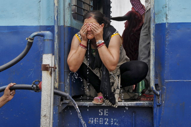 A passenger washes her face to cool herself off at a railway station on a hot summer day in Allahabad, June 11, 2015. (Photo by Jitendra Prakash/Reuters)