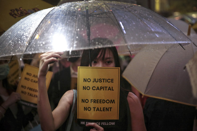 A woman holds an umbrella and a placard as people gather at Chater Garden to give support to the recent protests against the extradition bill, at the financial district in Hong Kong, Thursday, August 1, 2019. The Chinese army has released a promotional video for its Hong Kong-based troops at a time of uncertainty over whether the military will intervene in the city's summer of protest. (Photo by Elson Li/HK01 via AP Photo)