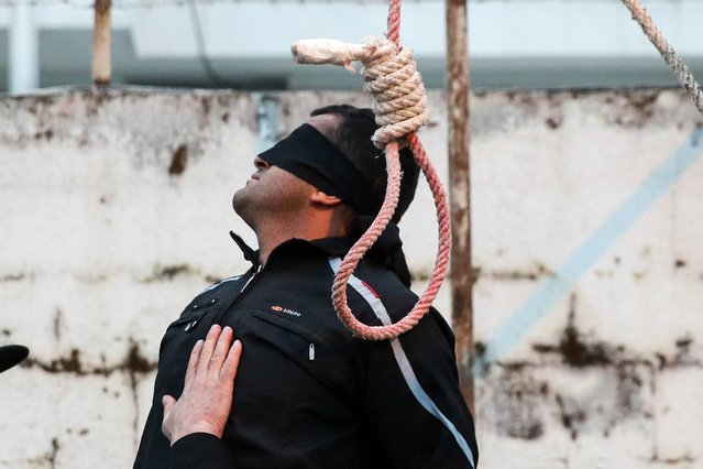 Balal, who killed Iranian youth Abdolah Hosseinzadeh in a street fight with a knife in 2007, is pictured blindfolded next to a noose during his execution ceremony in the northern city of Nowshahr on April 15, 2014. Samereh Alinejad, the mother of Abdolah Hosseinzadeh spared the life of Balal, her son's convicted murderer, with an emotional slap in the face as he awaited execution prior to removing the noose around his neck. (Photo by Araash Khamooshi/AFP Photo/ISNA)