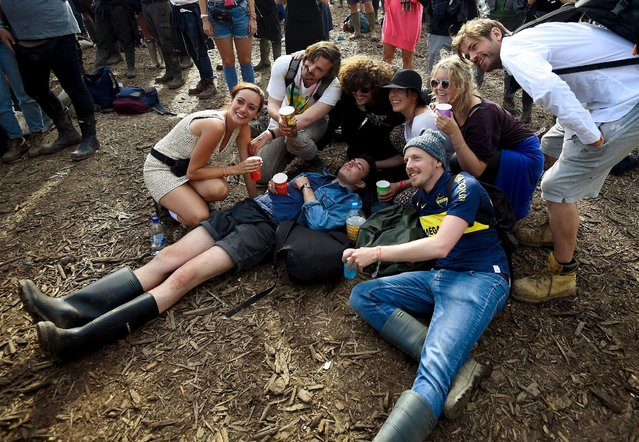 Revellers pose with one of their sleeping friends as they listen to music on the Other stage at Worthy Farm in Somerset during the Glastonbury Festival in Britain, June 28, 2015. (Photo by Dylan Martinez/Reuters)