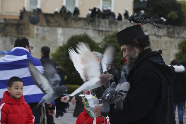 Tourists watch as a Christian orthodox monk, opponent of the Prespa Agreement, participating in a protest rally, feeds pigeons outside the Greek Parliament, in Athens, Friday, January 25, 2019. Greek lawmakers have ratified the agreement for the country to drop its objections to neighbouring Macedonia joining NATO if the small country's name is changed to North Macedonia, aiming to end a nearly three decade-long dispute that has kept Macedonia from joining the western military alliance and the European Union. (Photo by Petros Giannakouris/AP Photo)