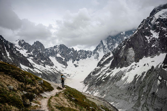 A man walks near the Mer de Glace glacier on the path to the Refuge du Couvercle (moutain hut) in Chamonix on June 18, 2019. In the Mont Blanc range, a magnet for mountaineers in the summer, many popular routes up or through the peaks have become too dangerous because of the risk of falling debris. (Photo by Marco Bertorello/AFP Photo)
