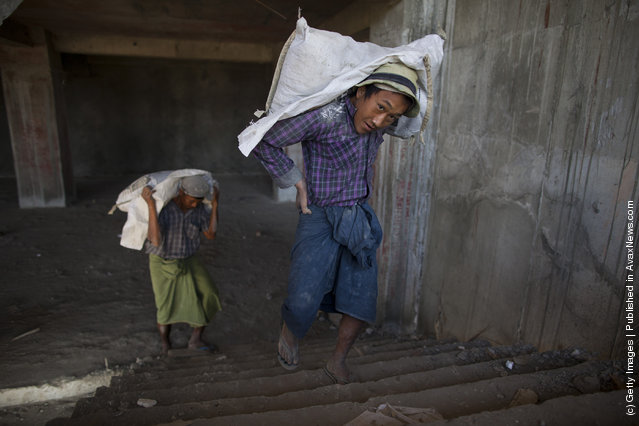 Burmese workers carry cement at a construction site for a new 140 room hotel