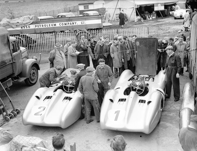 Mercedes Benz racing cars at Silverstone circuit. The Mercedes Benz team manager Alfred Neubauer (back, left) observes mechanics at work. United Kingdom, circa 1954. (Photo by Evening Standard/Getty Images)