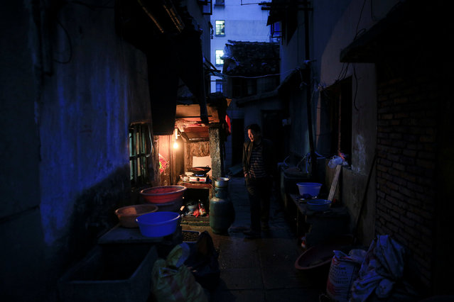 Bian Guohua stands outside his brother Bian Jianhua's place at Guangfuli neighbourhood in Shanghai, China, April 1, 2016. Bian Jianhua, 48, lives with his mother at an around 20-square-meter house in Guangfuli. (Photo by Aly Song/Reuters)