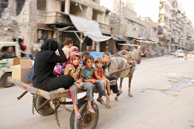 Civilians on a cart pulled by a horse travel along a street in Aleppo's Al-Shaar neighborhood June 27, 2015. (Photo by Abdalrhman Ismail/Reuters)