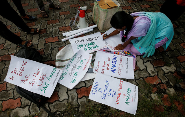 A student writes placards before a protest march demanding protection for the Amazon rainforest near the consulate of Brazil in Kolkata, India, August 26, 2019. (Photo by Rupak De Chowdhuri/Reuters)
