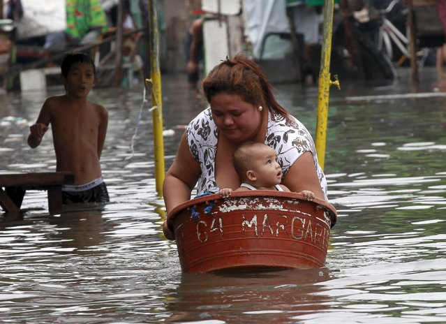 A mother puts her baby in a basin while she wades in waist-deep flooding caused by typhoon Linfa, locally named Egay, at Longos town in Malabon city, north of Manila July 6, 2015. (Photo by Romeo Ranoco/Reuters)