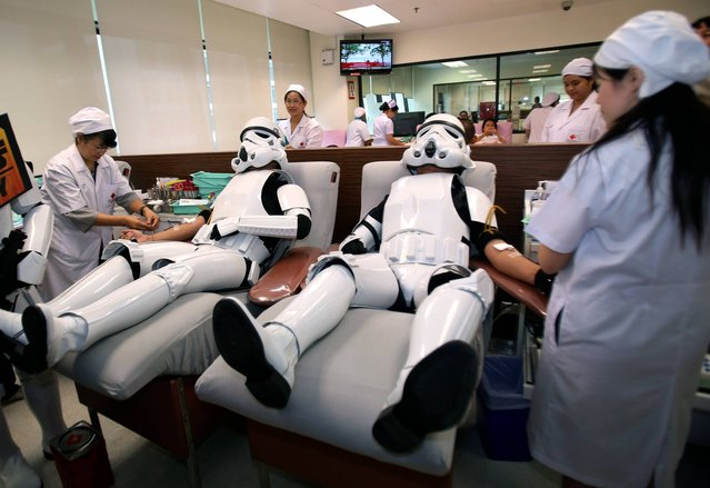 Udomsak Ratanotayo, left, and Suttinan Boonsomkiat wear storm trooper costumes while donating blood at the Thai Red Cross in Bangkok, Thailand on Monday, April 28, 2014. Thai Star Wars fans will donate blood and give toys at an orphanage as part of a promotional campaign. (Photo by Sakchai Lalit/AP Photo)