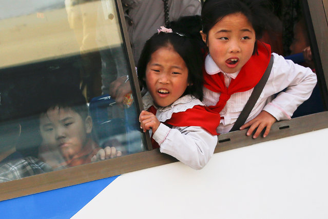 Girls look from inside a bus in central Pyongyang, North Korea April 16, 2017. (Photo by Damir Sagolj/Reuters)