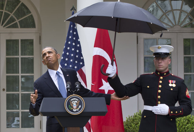 President Barack Obama leans out from under an umbrella to check if it's still raining, during a joint news conference with Turkish Prime Minister Recep Tayyip Erdogan, Thursday, May 16, 2013, in the Rose Garden of the White House in Washington. (Photo by Jacquelyn Martin/AP Photo)